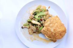 Uppståndelse stekte kryddig skaldjur med svartpeppar och thai stilomelett med ris på den vita maträtten, thailändsk kryddig örtma royaltyfri bild