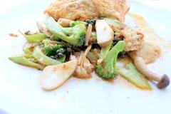 Uppståndelse stekte kryddig skaldjur med svartpeppar och thai stilomelett med ris på den vita maträtten, thailändsk kryddig örtma arkivbild
