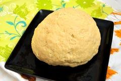 Uppstigen jästdeg för bröd eller pizza i en svart bakplåt på en färgbordduk Arkivfoto
