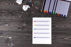 Uppsättning av blyertspennor på gamla bräden Färgpennor på ett ark av papper Royaltyfri Foto