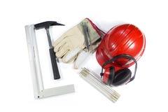 Uppsättning av byggnadshjälpmedel - den skyddande öronskydden, hammare, spikar, handskar, den skyddande hjälmen och hopfällbara l Arkivfoton