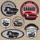 Uppsättning av emblem med den retro bilen på väggen Arkivbild