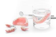 Uppsättning av tandprotesen i exponeringsglas av vatten och hjälpmedel på vit bakgrund Arkivfoto