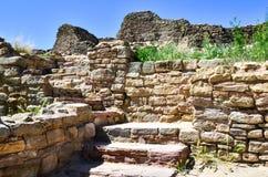 Upptäck att forntida väggar och en trappa till forntiden med guling blommar under en blå himmel royaltyfria bilder