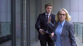 Upptagen affärsdam som ignorerar ung manlig anställd som frågar att underteckna rapporten, arbete stock video
