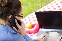 Upptagen affärskvinna i trädgård Royaltyfria Bilder