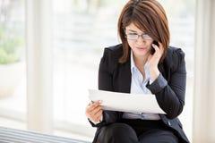 Upptagen affärskvinna på telefonen arkivbild