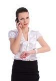 Upptagen affärskvinna som kontrollerar tid, medan tala på Royaltyfri Fotografi
