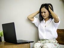Upptagen asiatisk affärskvinna ingen idé som rymmer huvudet med handen med huvudvärk, bekymmer och den olyckliga framsidan arkivbild