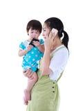 Upptagen asiatisk moder som använder smartphonen och bär hennes dotter I Royaltyfri Foto