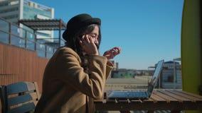 Upptagen flicka som arbetar utanför i solig vårdag stock video