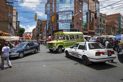 Upptagen genomskärning med bilar, bussar och folk i staden av La Paz, i Bolivia Arkivbilder