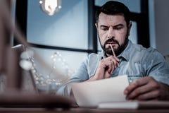 Upptagen hållande panicle för den fundersamma mannen nära skvallrar att läsa brevet arkivfoton