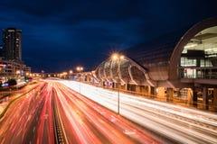 Upptagen huvudväg bredvid drevstationen under nattetid royaltyfria foton