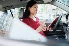 Upptagen kinesisk affärskvinna som arbetar i bil med minnestavlan arkivfoto
