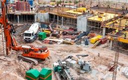 Upptagen konstruktionsplats med maskineri och arbetare Fotografering för Bildbyråer