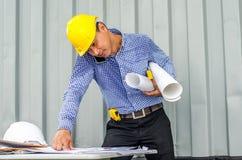 Upptagen konstruktionstekniker som talar på telefonen, medan bära ritningar med att kontrollera byggnadsframsteget arkivfoto