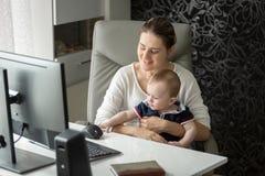 Upptagen kvinna som hemma arbetar på datoren och tar omsorg av hennes lodisar Arkivbild