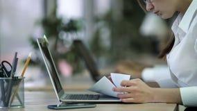 Upptagen kvinna som kontrollerar viktiga dokument, analyserar och bearbetar information Arkivfoto