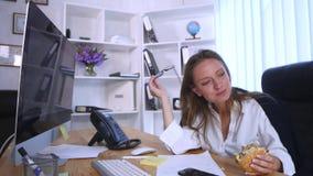 Upptagen kvinna som talar på telefonen, medan ha hamburgaren arkivfilmer