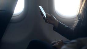 Upptagen kvinnainnehavtelefon i hand och sitta i flygplan arkivfilmer