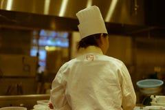 Upptagen kvinnlig kock som ses från baksidan i en japansk restaurang, Tokyo, Japan royaltyfri fotografi