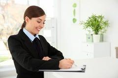 Upptagen kvinnlig receptionist på arbetsplatsen fotografering för bildbyråer
