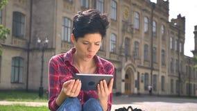 Upptagen läsning för ung kvinna på minnestavlan och det tänkande lyftande huvudet upp och le på kameran som nära sitter på gatan lager videofilmer