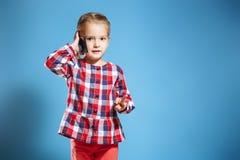 Upptagen liten flicka som talar på mobiltelefonen på blå bakgrund royaltyfri fotografi