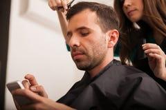 Upptagen man i en hårsalong Royaltyfri Foto