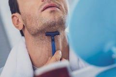 Upptagen man som skrapar hans hals, medan raka i badrummet fotografering för bildbyråer