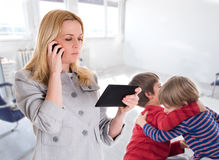 Upptagen moder med minnestavlan och mobilen medan hennes barn Arkivfoto
