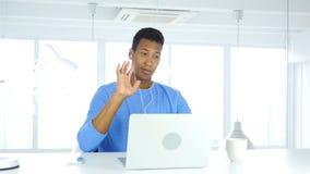 Upptagen online-video pratstund för man på bärbara datorn på arbete Royaltyfri Foto