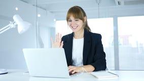Upptagen online-video pratstund på bärbara datorn på arbete av den unga kvinnlign Royaltyfri Foto