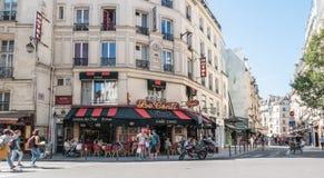 Upptagen Paris gataplats framme av Le Kafé Conti Arkivbilder