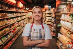 Upptagen ställning för ung kvinna i linje mellan shelfs med pasta Hon poserar på kamera och leende Lycklig positiv modell royaltyfri foto