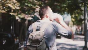 Upptagen stilig europeisk man som går ner trappan av ett Brooklyn hus med smartphone- och kaffeultrarapidnärbild stock video