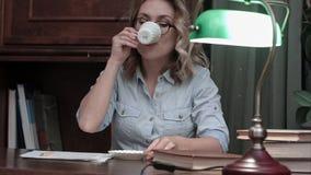 Upptagen student i exponeringsglasarbete på hennes rapport på skrivbordet med en grön lampa som går till och med böcker och drick royaltyfria bilder