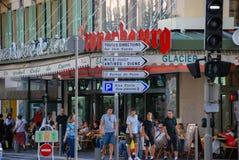 Upptagen trafik av folk på gatorna ljusa Nice, azur seglar utmed kusten I Royaltyfri Bild