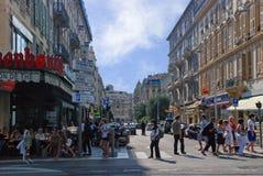 Upptagen trafik av folk på gatorna ljusa Nice, azur seglar utmed kusten I Arkivbilder
