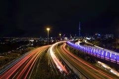 Upptagen trafik längs huvudvägen på natten på Auckland, Nya Zeeland royaltyfri foto