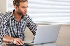 Upptagen ung caucasian vuxen man genom att använda en bärbar dator och en mus Royaltyfri Bild
