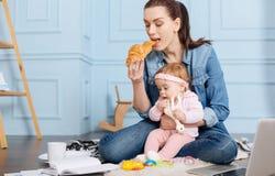Upptagen uppfinningsrik mamma som äter frunch med hennes dotter Arkivbilder