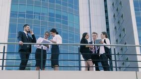 Upptaget affärsfolk utomhus på terrassen av en kontorsbyggnad