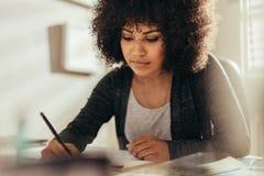 Upptaget arbete för kvinnlig arkitekt på hennes skrivbord arkivbild