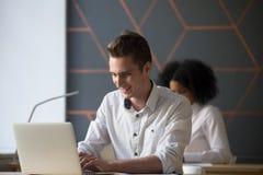 Upptaget arbete för lycklig millennial arbetare på bärbara datorn i regeringsställning royaltyfri fotografi