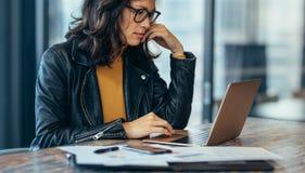 Upptaget kvinnasammanträde på skrivbordet och arbete på bärbara datorn royaltyfri fotografi