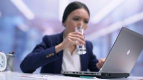 Upptaget kvinnligt anställddricksvatten från den sittande kontorstabellen för exponeringsglas, uppfriskning stock video