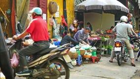 Upptaget lokalt dagligt liv av morgongatamarknaden i Hanoi, Vietnam En upptagen folkmassa av säljare och köpare i marknaden stock video