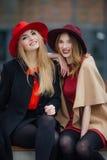 Upptaget sammanträde för kvinna två på bänken som talar med de Royaltyfria Bilder